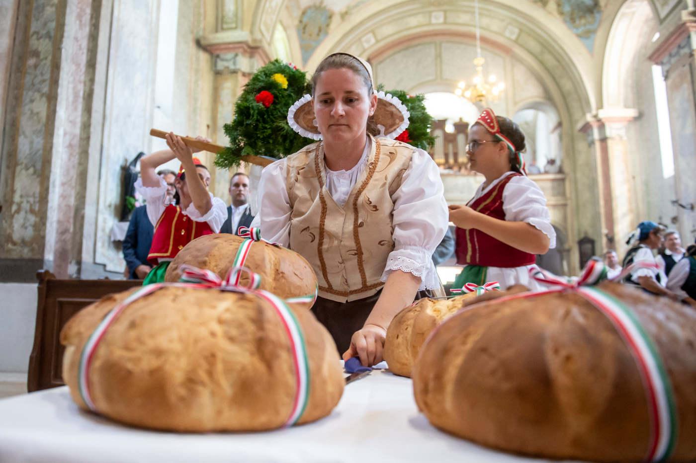 Népviseletbe öltözött asszony az új kenyereket helyezi el az államalapítás és az államalapító Szent István király ünnepén a kemencei római katolikus Kisboldogasszony templomban tartott szentmisén 2020. augusztus 20-án. MTI/Komka Péter